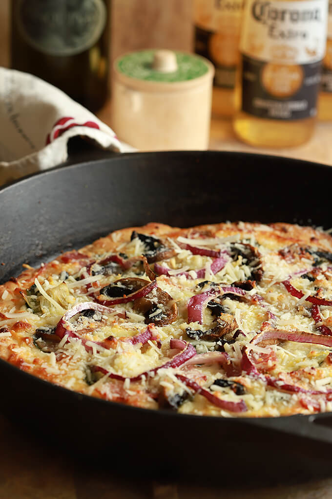 Artichoke, Spinach, Mushroom, and Bacon Pizza in a Black Cast Iron Skillet