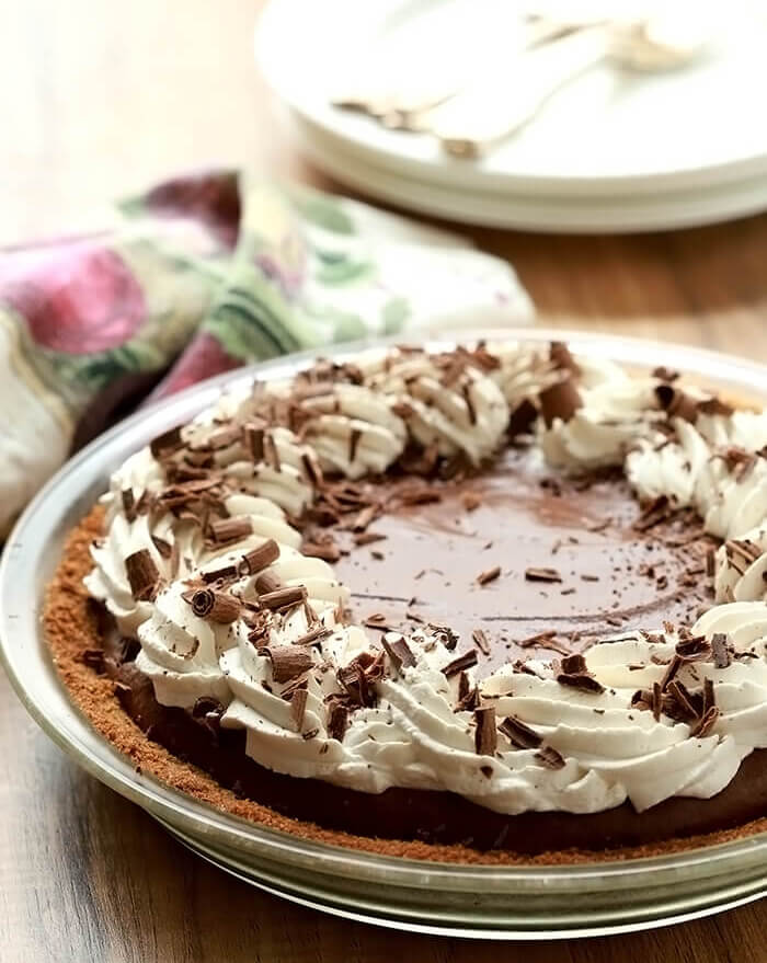 French Silk Pie with Bourbon topped with whipped cream and chocolate curls.