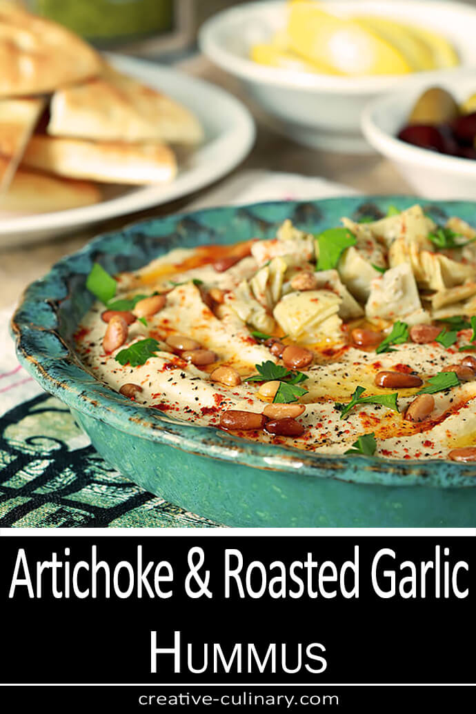 Artichoke and Roasted Garlic Hummus in a Teal Serving Bowl with Pita Chips on the Side
