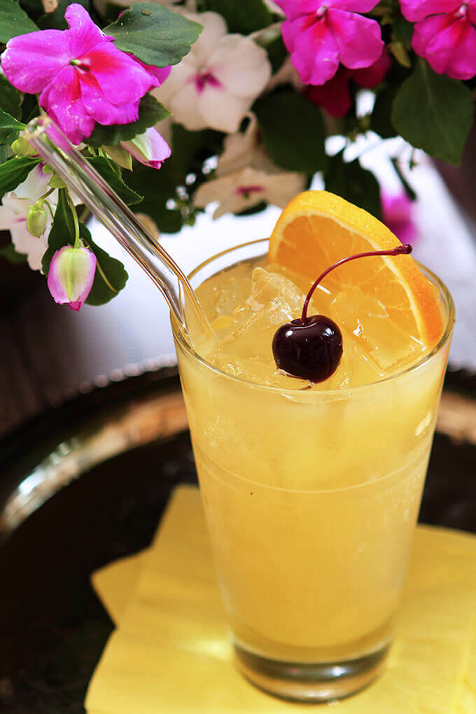 The Black-Eyed Susan Cocktail - Signature Cocktail for the Preakness Served on a Tray with Orange and Cherry Garnishes