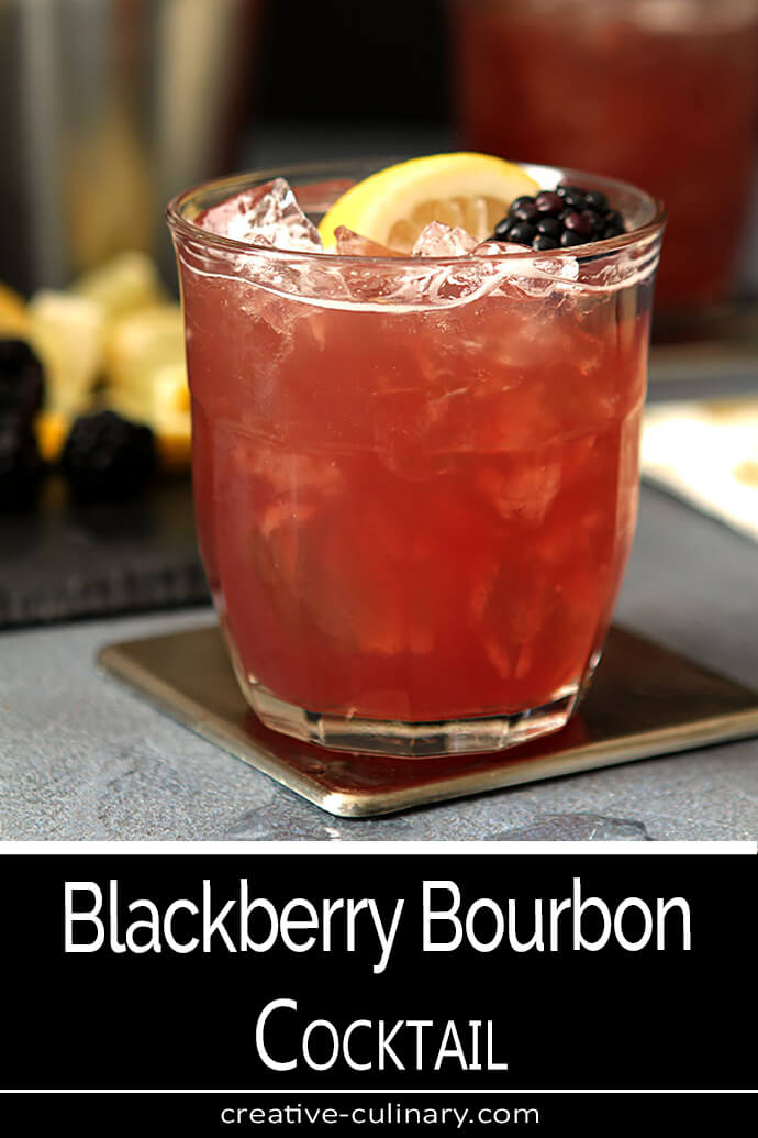 Blackberry Bourbon Cocktail in a Lowball Glass Garnished with a Lemon Slice and a Blackberry