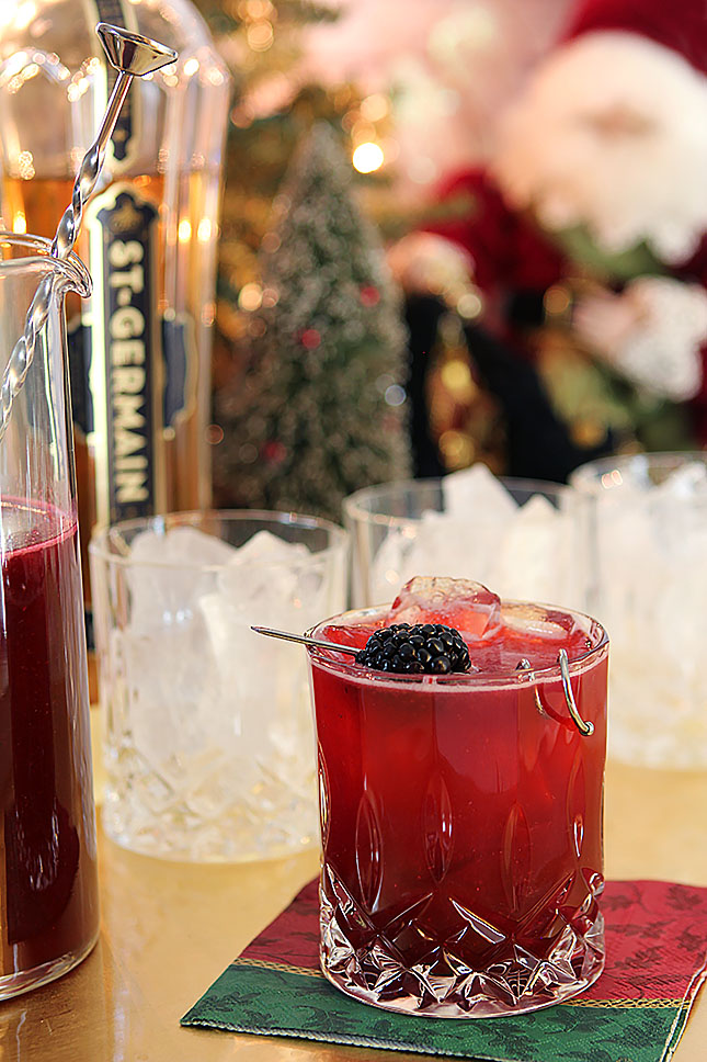 Blackberry Collins Cocktail with St. Germain Liqueur on a Napkin with a Christmas Scene