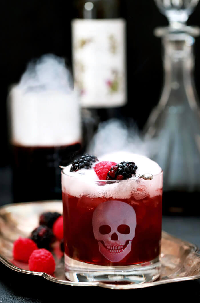 Blackberry Smash Halloween Cocktail Served in a Glass with an Etched Skull and Dry Ice