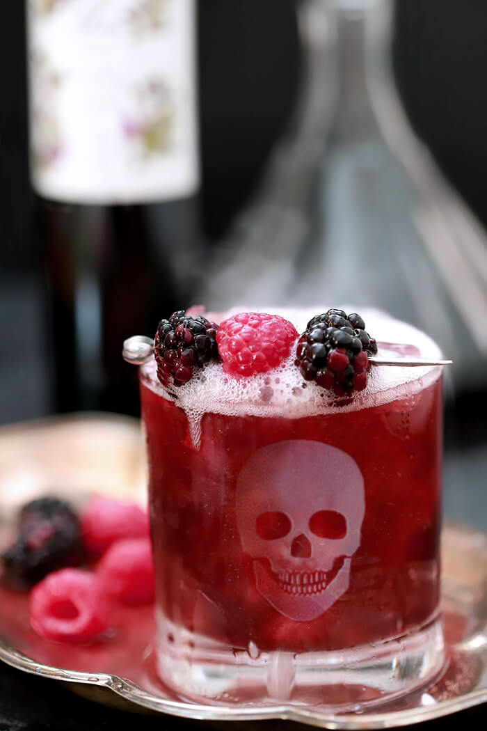 Blackberry Smash Halloween Cocktail Served on a Tray with Berries and Bubbly Prosecco