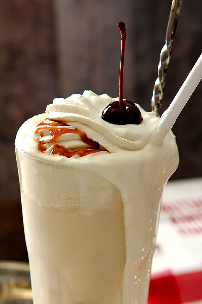 Boozy Salted Caramel Milkshake served in a tall glass, drizzled with caramel and topped with whipped cream and a cherry.
