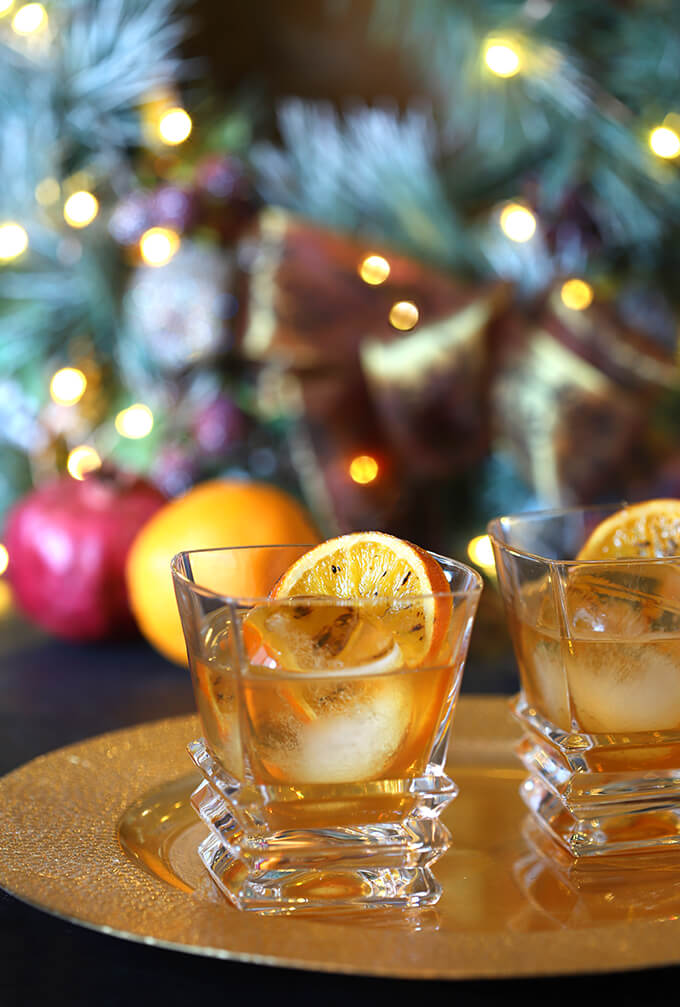 Bourbon and Orange Brulee Cocktails by a Christmas Tree