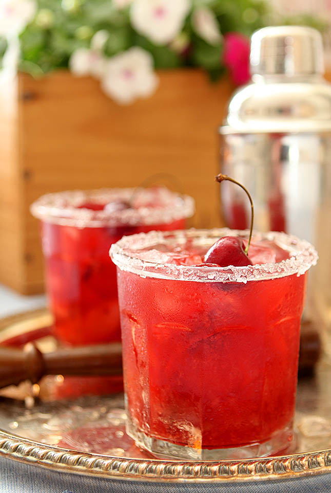 Two Glasses Garnished with a Bing Cherry for a Cherry Smash