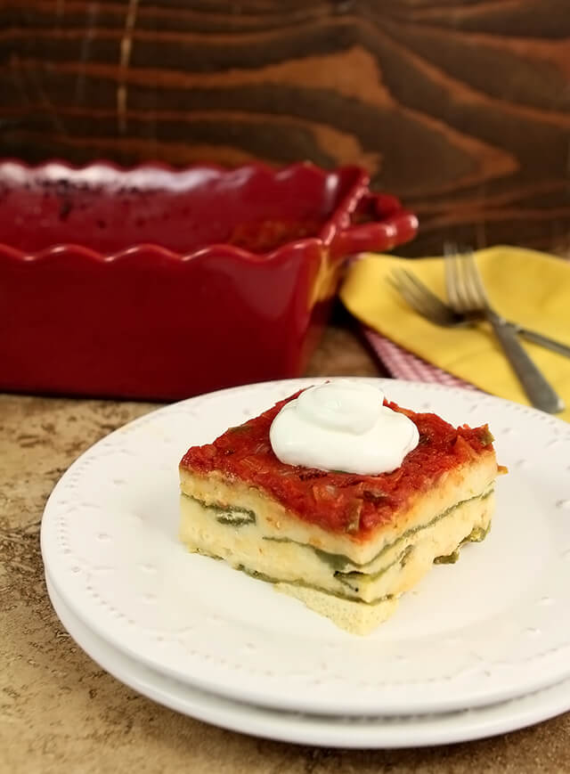 Chile Relleno Casserole served on a white plate with a dollop of sour cream on top.