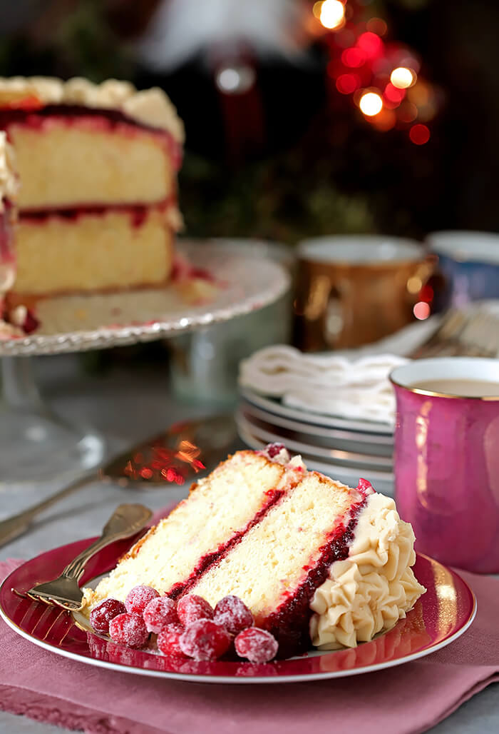 Slice of Orange Cake with Brown Sugar Buttercream and Cranberry Glaze Garnished with Sugared Cranberries