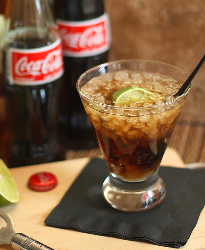 Cuba Libre Cocktail Seved in a Short Glass with Lime Wedge