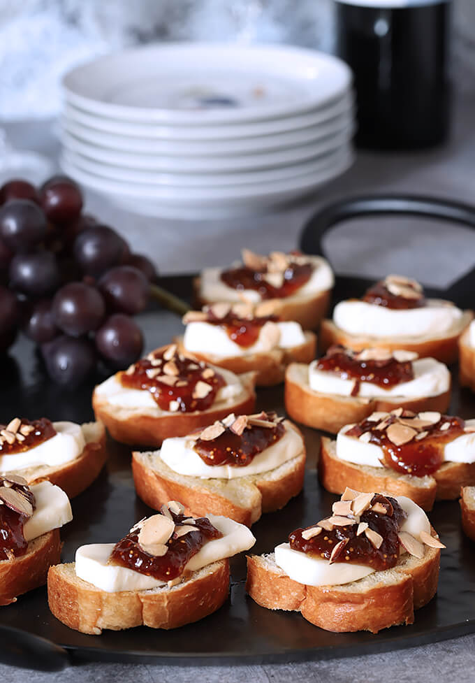 Fig Jam and Brie Crostini Appetizer with Toasted Almonds on a Serving Tray