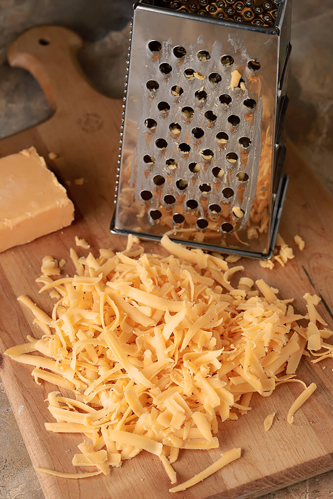 Grated Cheddar Cheese with Cheese Grater on a Bread Board