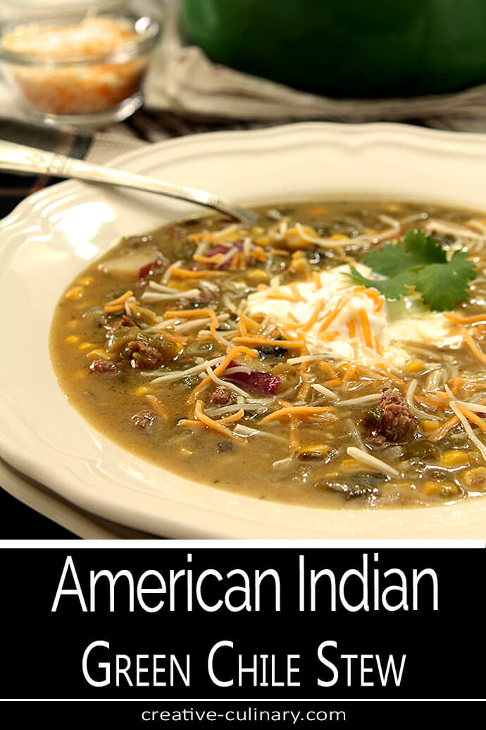 American Indian Green Chile Stew Served with Sour Cream and Cheese Garnish in a Wide White Bowl
