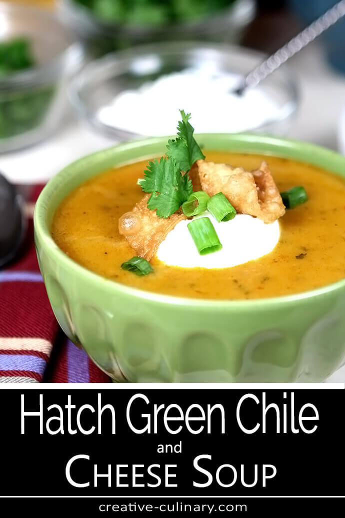 Hatch Green Chile and Cheese Soup Served in a Green Ceramic Bowl and Garnished with Sour Cream and Tortilla Chips