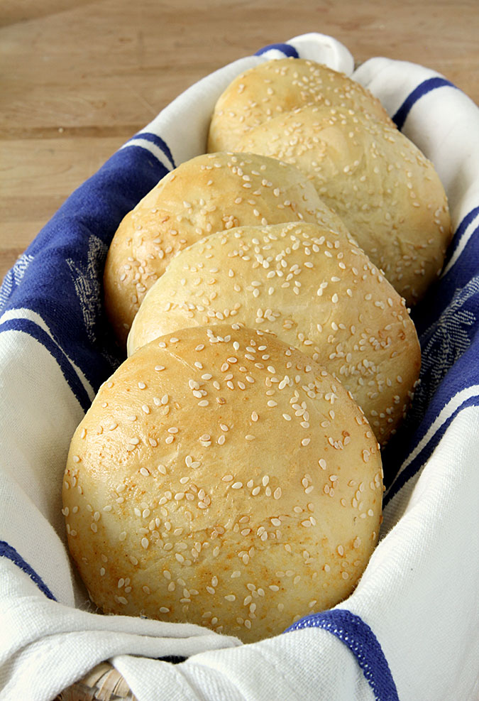 Homemade Hamburger Buns with Sesame Seeds in a Basket with Blue and White Towel