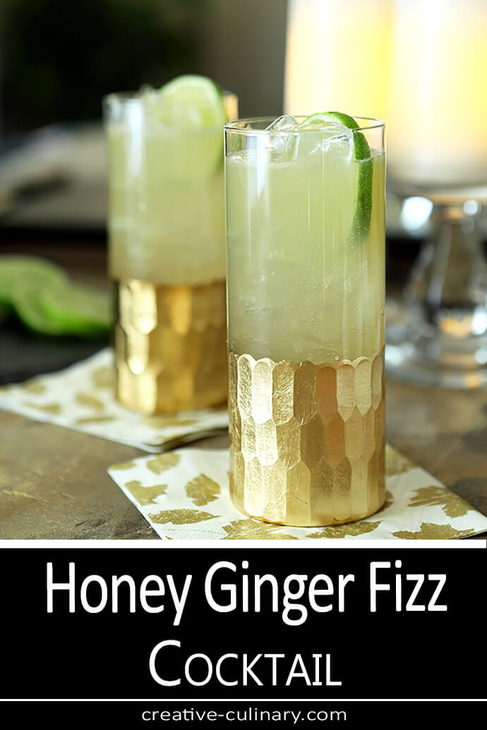 Honey Ginger Fizz Cocktail served in a tall glass embellised with gold leaf and garnished with a lime slice.