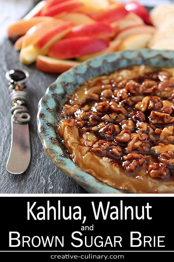 Kahlua, Walnut, and Brown Sugar Brie is Served warm in a turquoise pottery dish.