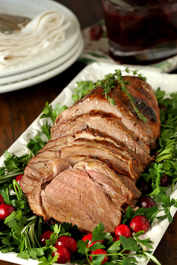 Roasted Lamb with Honey Thyme Glaze Sliced on a Serving Platter and Garnished with Greens and Fresh Cranberries