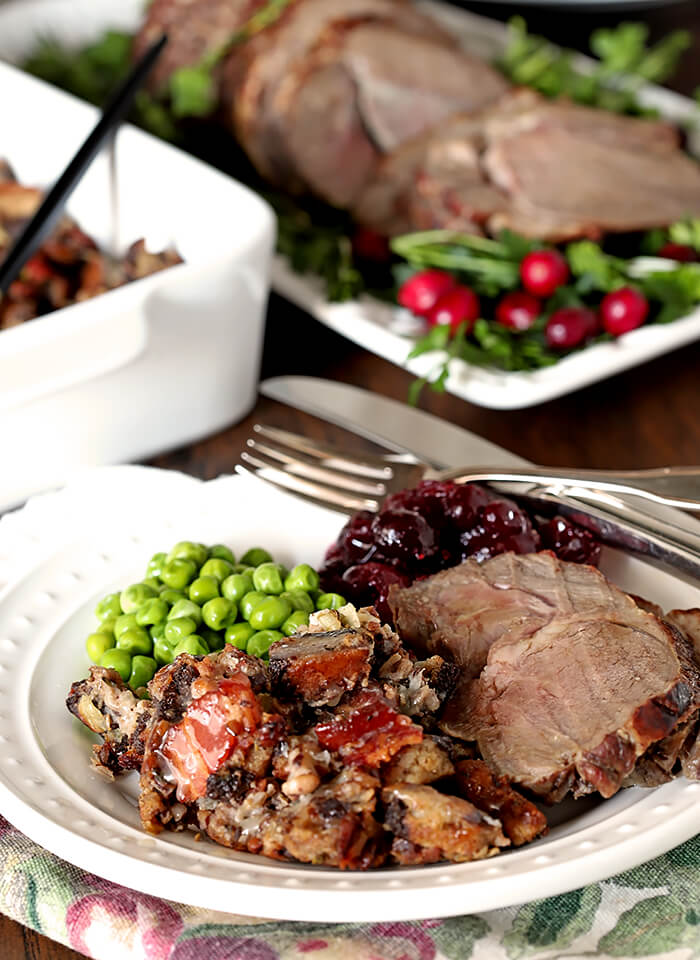 Roasted Lamb with Honey Thyme Glaze Served with Dressing, Peas, and Cranberry Sauce