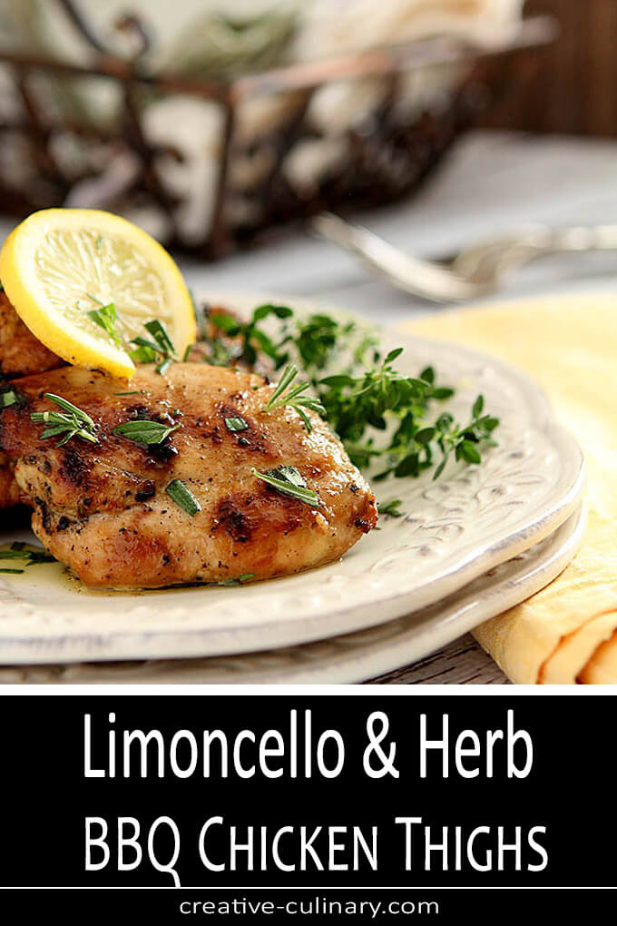 Limoncello and Herb Barbecue Chicken Thighs Served on a Plate and Garnished with Fresh Herbs and Lemon