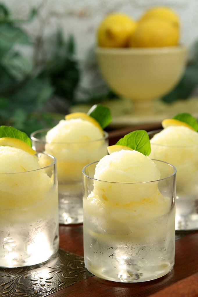 Frozen Limoncello Sorbet Served in Short Glasses with Mint and Lemon Slice Garnish