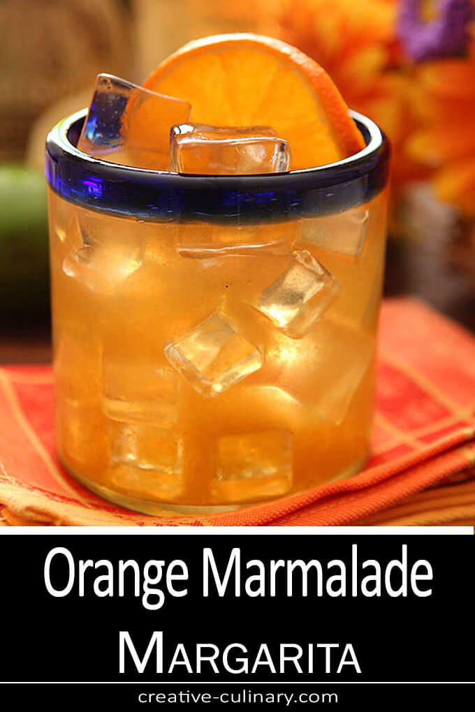 Orange Marmalade Margarita in a Short Glass with a Blue Rim and Garnished with an Orange Wheel.
