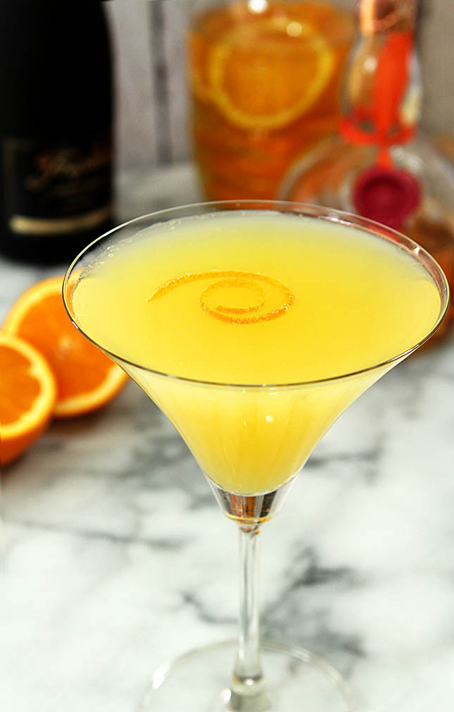 Orange Sunshine Martini on a Marble tabletop and garnished with an orange twist.
