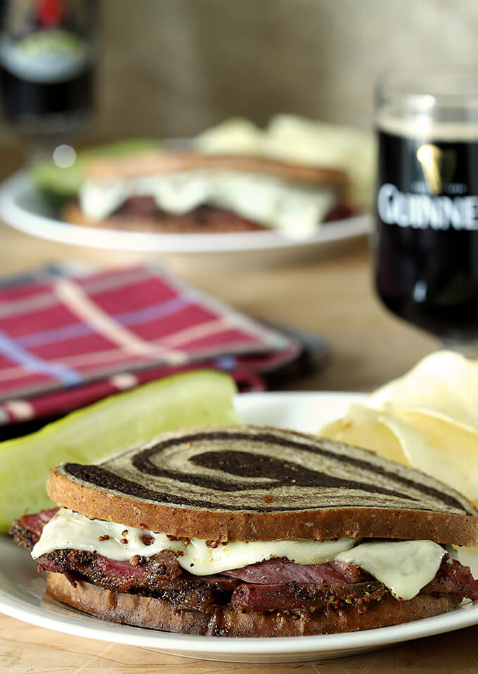 Home Cured Pastrami on Rye Sandwiches with Swiss Cheese served on a plate; Guinness beer in the background.