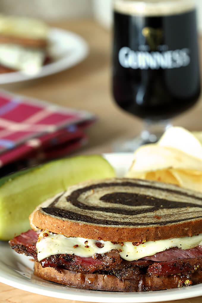 Home Cured Pastrami on Rye Sandwiches with Swiss Cheese on a Plate with a Glass of Guinness Beer