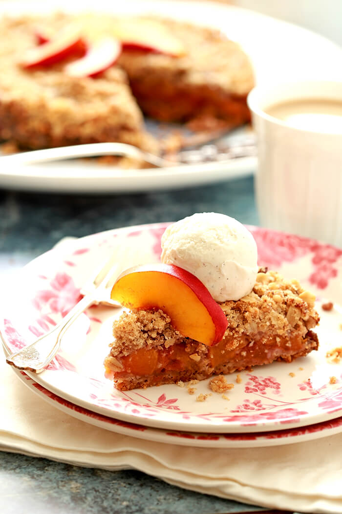 Slice of Fresh Double Crusted Peach and Pecan Crisp on a White Plate with Pink Decorations