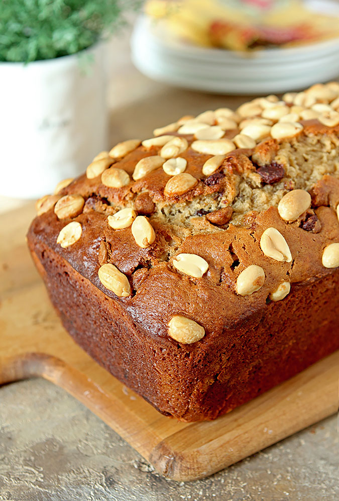 Peanut Butter is mixed with Banana Bread and Milk Chocolate Chips and shown on a wooden cutting board.