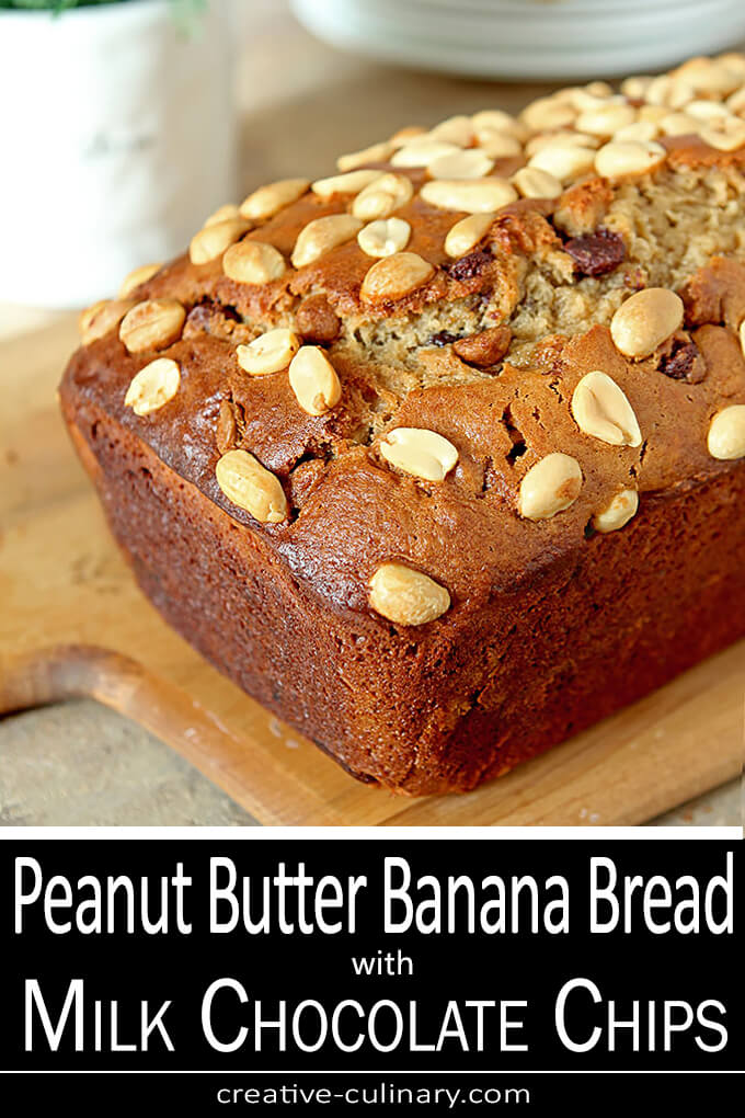 Banana Bread on Cutting Board with peanut halves on top of loaf.
