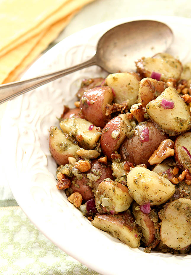 Pesto Potato Salad with Parmesan Toasted Walnuts in a White Dish.