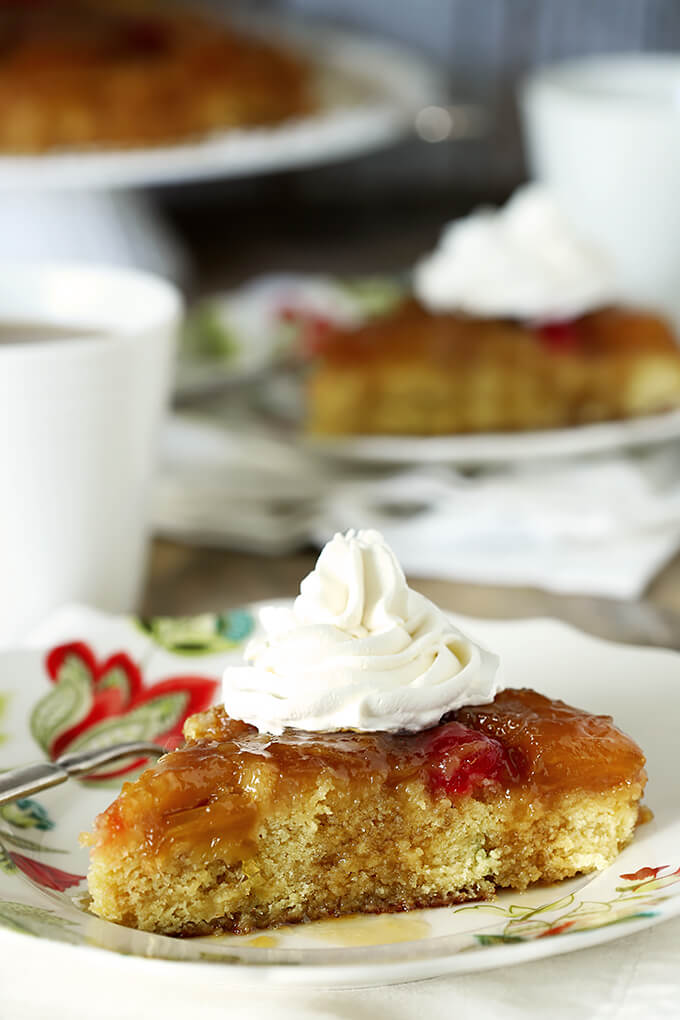 The Best Pineapple Upside Down Cake with Rum on a Plate with Whipped Cream