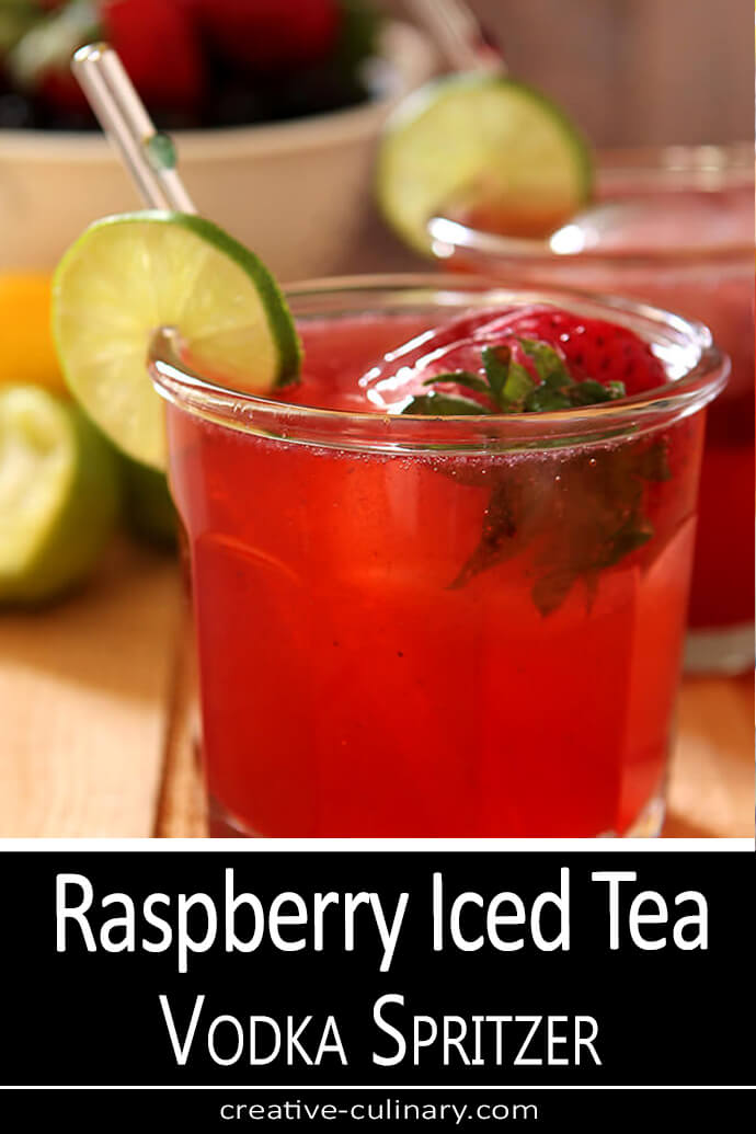 Raspberry Iced Tea Vodka Spritzer in a lowball glass with a strawberry ice cube and lime slice.