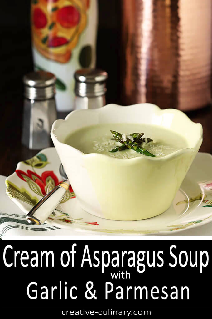 Cream of Asparagus Soup Served in a White and Yellow Bowl with both Asparagus Spear and Parmesan Garnish