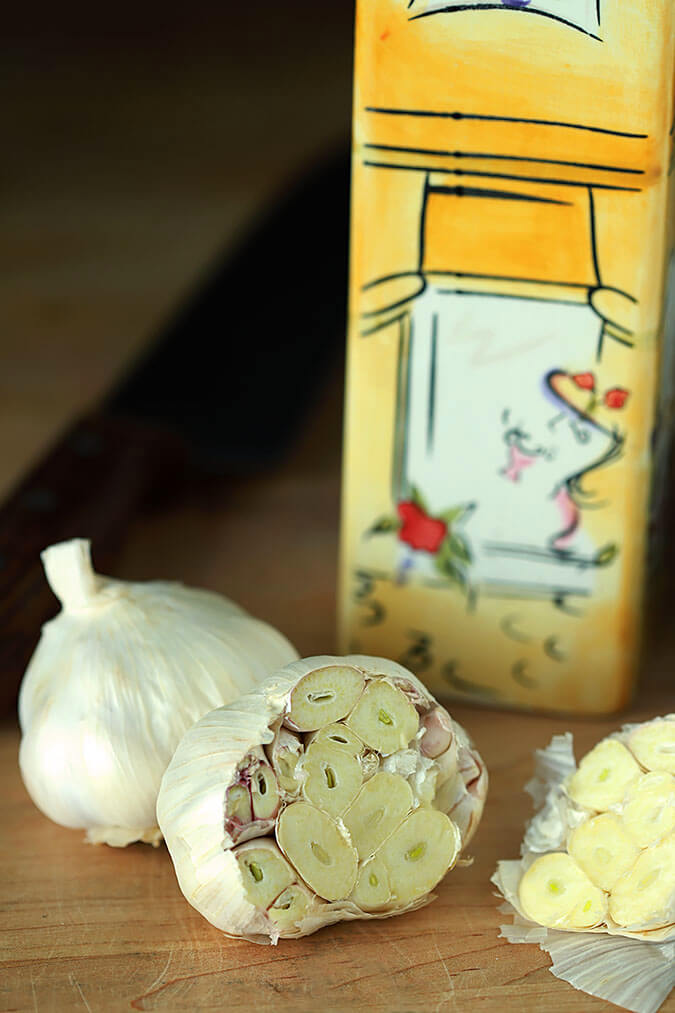 Raw garlic is sliced open on top ready to be put into a baking dish.