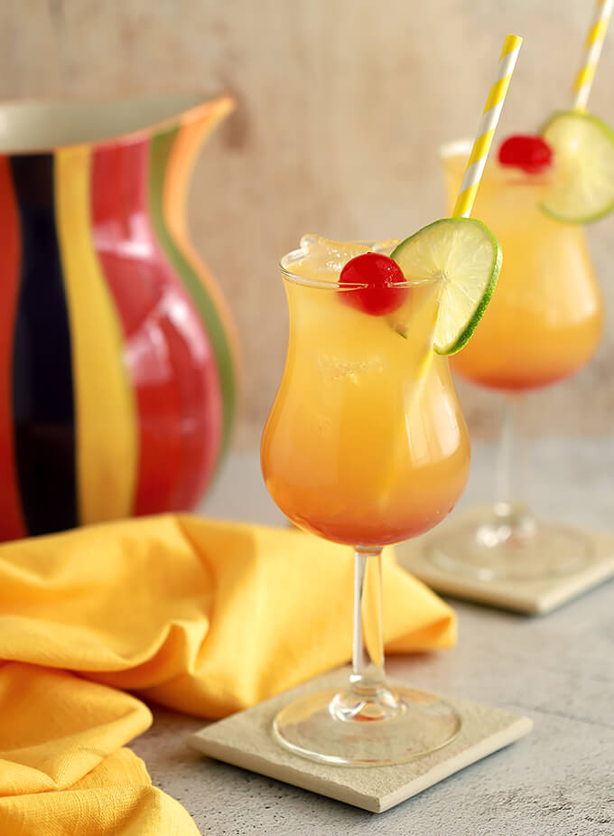 Classic Rum Punch Cocktail combines three rums and two juices in a hurricane glass.