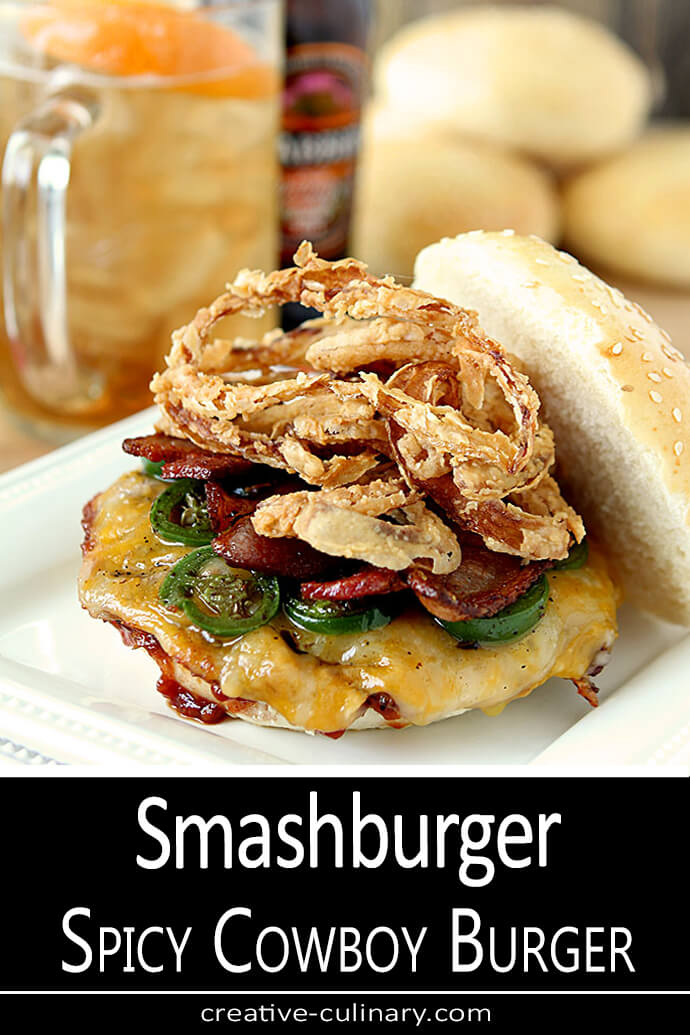 Smashburger Spicy Cowboy Burger topped with fried onion rings and served on a white plate.