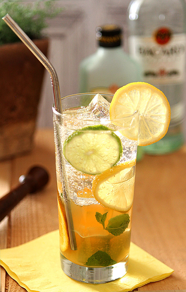 Mixed Citrus Mojito with Limoncello Served in a Tall Glass with a Stainless Straw and Garnished with Lemon and Lime